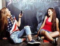 De nuevo a escuela después de vacaciones de verano, dos muchachas reales adolescentes en sala de clase con la pizarra pintada jun Imagen de archivo