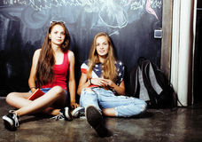 De nuevo a escuela después de vacaciones de verano, dos muchachas reales adolescentes en sala de clase con la pizarra pintada jun Fotos de archivo