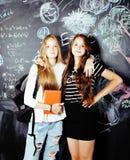 De nuevo a escuela después de vacaciones de verano, dos muchachas reales adolescentes en sala de clase con la pizarra pintada jun Foto de archivo