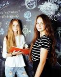 De nuevo a escuela después de vacaciones de verano, dos muchachas reales adolescentes en sala de clase con la pizarra pintada jun Imagenes de archivo