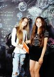 De nuevo a escuela después de vacaciones de verano, dos muchachas reales adolescentes en sala de clase con la pizarra pintada jun Fotografía de archivo