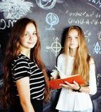 De nuevo a escuela después de vacaciones de verano, dos muchachas reales adolescentes en sala de clase con la pizarra pintada jun Imágenes de archivo libres de regalías