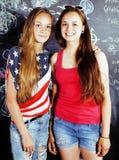 De nuevo a escuela después de vacaciones de verano, dos muchachas reales adolescentes en sala de clase con la pizarra pintada jun Fotografía de archivo libre de regalías