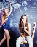 De nuevo a escuela después de vacaciones de verano, dos muchachas adolescentes en sala de clase con la pizarra pintada Fotos de archivo libres de regalías