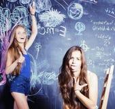 De nuevo a escuela después de vacaciones de verano, dos muchachas adolescentes en sala de clase con la pizarra pintada Fotografía de archivo libre de regalías