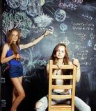 De nuevo a escuela después de vacaciones de verano, dos muchachas adolescentes en sala de clase con la pizarra pintada junto Imágenes de archivo libres de regalías