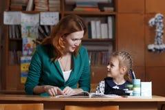 De nuevo a escuela El niño está aprendiendo escribir La mujer adulta enseña niño al alfabeto Imagen de archivo