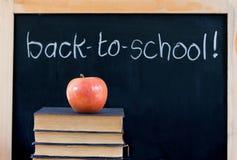 De nuevo a escuela en la pizarra con la manzana y los libros Imagen de archivo