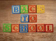 De nuevo a escuela en la tabla de madera Imagen de archivo