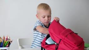 De nuevo a escuela Niño pequeño lindo que pone el libro a su bolso Ni?o de la escuela primaria metrajes