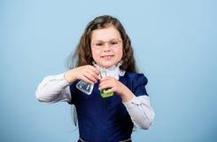 De nuevo a escuela Peque?o cient?fico de la muchacha con el frasco de prueba Educaci?n y conocimiento Lecci?n del bilogy del estu imágenes de archivo libres de regalías