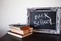 De nuevo a escuela, tiza en un marco del vintage Texto en la pizarra y una pila de libros de texto imagen de archivo