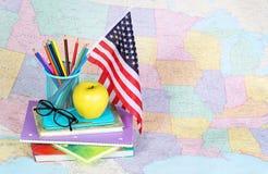 De nuevo a escuela Una manzana, lápices coloreados, bandera americana Fotos de archivo