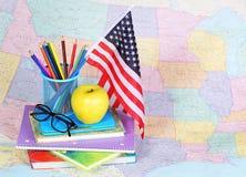 De nuevo a escuela Una manzana, lápices coloreados, bandera americana Imagen de archivo