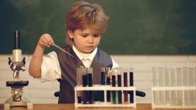 De nuevo a escuela y a tiempo feliz el ni?o est? aprendiendo en clase en el fondo de la pizarra Ciencia de la qu?mica Lecci?n de  almacen de video