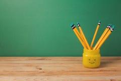 De nuevo a fondo de la escuela con los lápices en tarro del emoji en la tabla de madera Foto de archivo libre de regalías