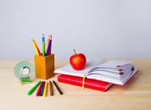 De nuevo a fondo de la escuela con los libros, los lápices y la manzana sobre la tabla de madera imagen de archivo