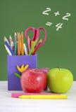 De nuevo a la caja de lápiz de la escuela contra la pizarra verde Fotos de archivo libres de regalías