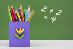 De nuevo a la caja de lápiz de la escuela contra la pizarra verde Imágenes de archivo libres de regalías