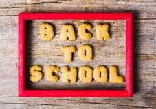 De nuevo a la escuela escrita con las galletas en la tabla de madera foto de archivo libre de regalías