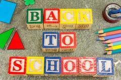 De nuevo a la escuela escrita con las letras cúbicas de madera Fotos de archivo libres de regalías