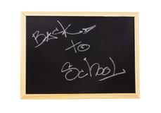 de nuevo a la escuela escrita en la pizarra aislada en el fondo blanco Imágenes de archivo libres de regalías