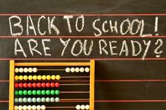 De nuevo a la escuela escrita en la pizarra y el ábaco Fotografía de archivo