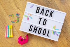 De nuevo a la escuela escrita en una caja de luz moderna en el fondo de madera, fuentes coloridas Fotografía de archivo libre de regalías