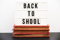 De nuevo a la escuela escrita en una caja de luz en una pila de libros viejos Fotos de archivo