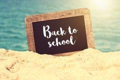 De nuevo a la escuela escrita en una pizarra del vintage en la arena de una playa Imagen de archivo