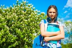 De nuevo a la muchacha del adolescente del estudiante de la escuela que sostiene los libros y los cuadernos que llevan la mochila Fotografía de archivo libre de regalías