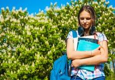 De nuevo a la muchacha del adolescente del estudiante de la escuela que sostiene los libros y los cuadernos que llevan la mochila Fotos de archivo