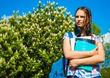 De nuevo a la muchacha del adolescente del estudiante de la escuela que sostiene los libros y los cuadernos que llevan la mochila Imagenes de archivo