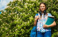 De nuevo a la muchacha del adolescente del estudiante de la escuela que sostiene los libros y los cuadernos que llevan la mochila Fotos de archivo libres de regalías