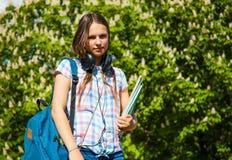 De nuevo a la muchacha del adolescente del estudiante de la escuela que sostiene los libros y los cuadernos que llevan la mochila Imagen de archivo libre de regalías