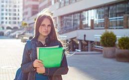 De nuevo a la muchacha del adolescente del estudiante de la escuela que sostiene los libros y los cuadernos que llevan la mochila imágenes de archivo libres de regalías