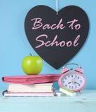 De nuevo a la pizarra del corazón de la escuela con efectos de escritorio rosados y coloridos brillantes Imagen de archivo libre de regalías