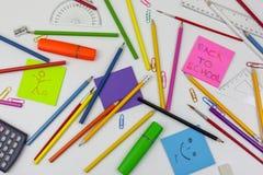 De nuevo a los lápices de la nota y del colorante de la escuela en un escritorio blanco Foto de archivo libre de regalías