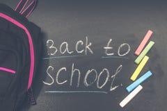 De nuevo a mensaje de la escuela en la pizarra inscrita con la tiza colorida para el fondo petate fotos de archivo