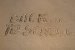 De nuevo a muestra de la escuela en la arena de la playa Foto de archivo libre de regalías
