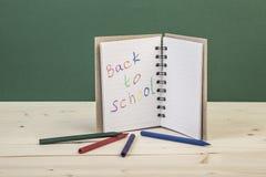 De nuevo a plantilla de la escuela con un cuaderno y creyones coloridos Foto de archivo