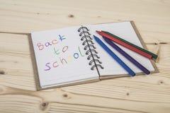 De nuevo a plantilla de la escuela con un cuaderno y creyones coloridos Fotografía de archivo