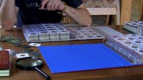 De numismaticus onderzoekt muntstukinzameling stock video