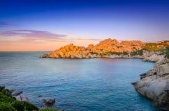 De oceaan rotsachtige mening van de kustlijn kleurrijke zonsondergang, Sardinige Royalty-vrije Stock Foto's