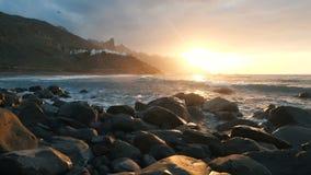 De oceaangolven verpletteren op rotsen en nevel in mooi zonsonderganglicht in langzame motie bij Benijo-strand in Tenerife, Kanar stock video