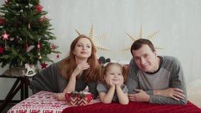 De ochtend van Kerstmis De jonge familie speelt gelukkig met elkaar Op het bed heel wat hoofdkussens, Kerstmisgiften binnen stock video