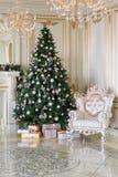 De ochtend van Kerstmis klassieke flats met een witte open haard, verfraaide boom, heldere bank, grote vensters Stock Foto