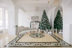 De ochtend van Kerstmis klassieke luxeflats met een witte open haard, verfraaide boom, heldere bank, grote vensters Stock Fotografie