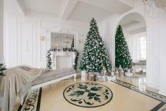 De ochtend van Kerstmis klassieke luxeflats met een witte open haard, verfraaide boom, heldere bank, grote vensters Stock Foto