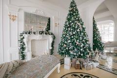 De ochtend van Kerstmis klassieke luxeflats met een witte open haard, verfraaide boom, heldere bank, grote vensters Stock Foto's